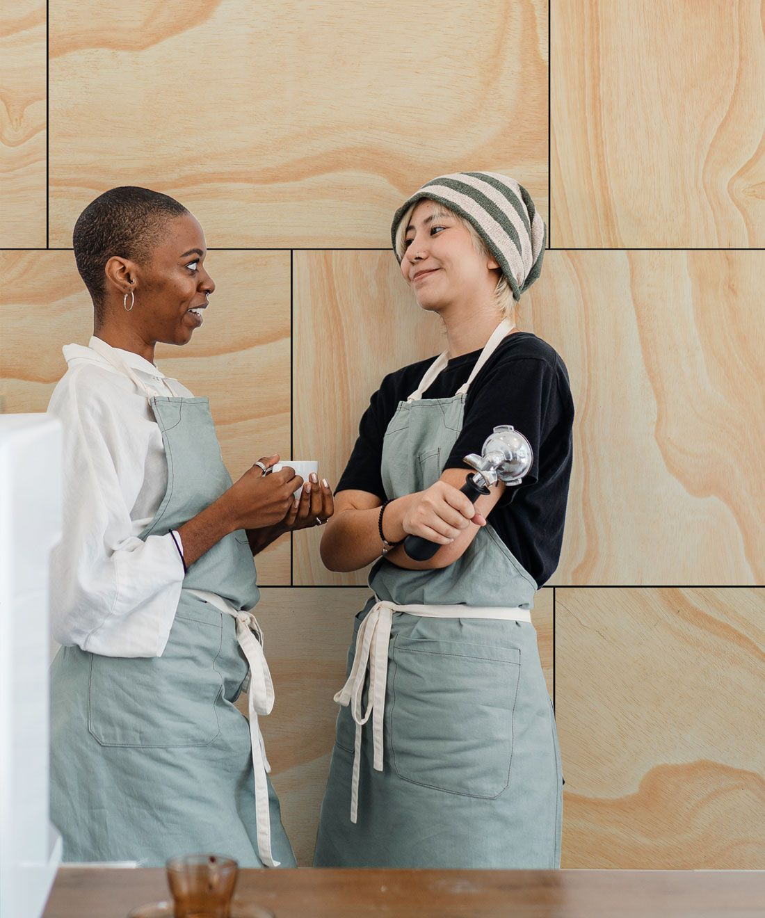 Ply Wood Wallpaper • Light Brown Wallpaper •Wood Grain Wallpaper with two co-workers leaning against the wall conversing