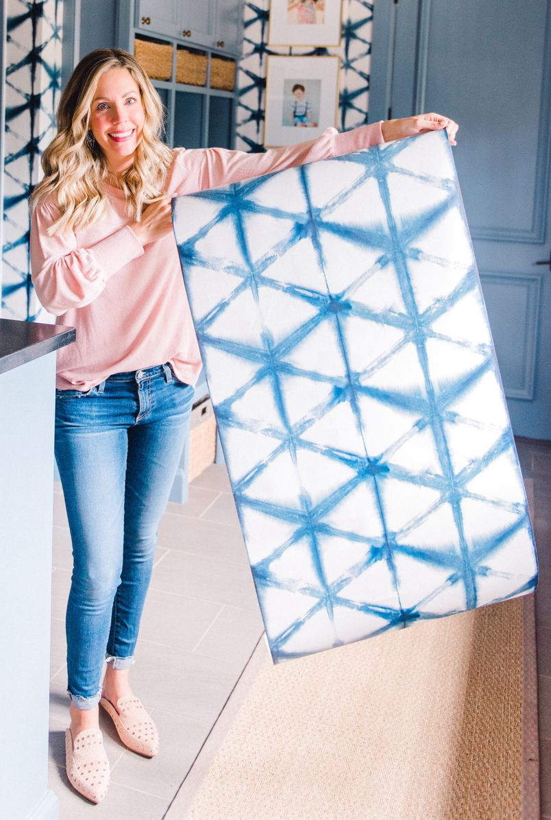 Ashley Massegee from the Curls & Cashmere Blog is holding her Shibori Star Wallpaper from Milton & King. This is a blog with important information for wallpaper first-timers
