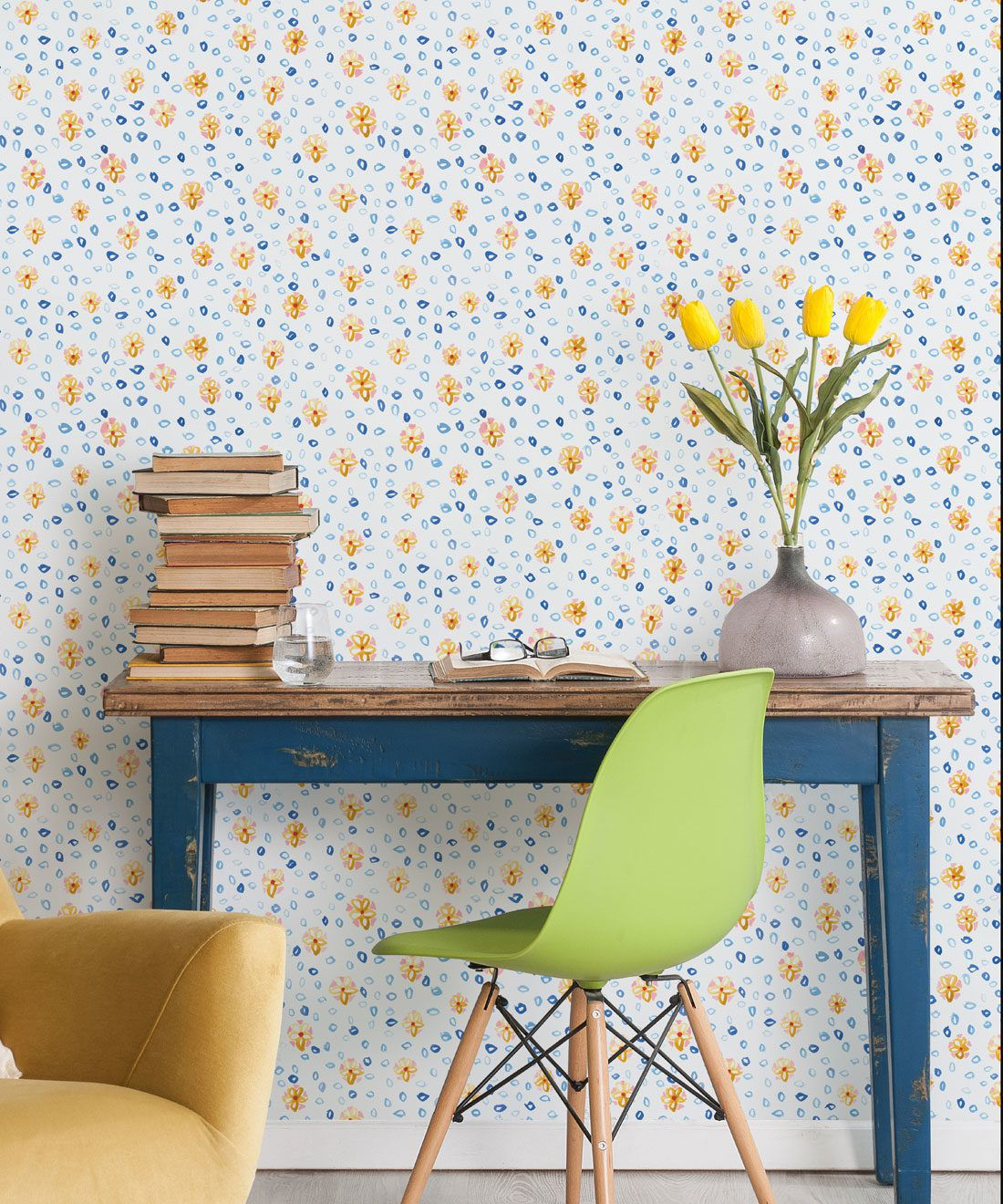 Al Hadiqa Wallpaper • Dainty Floral Design • Desk with books stacked on the left and a lime green chair in front with yellow tulips in a vase on the right side of the desk. • Milton & King Europe