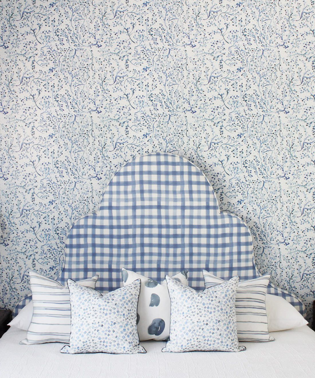 Indigo Garden • Blue Botanical Wallpaper • Floral • Bedroom with plaid blue headboard and white pillows. Milton & King Europe