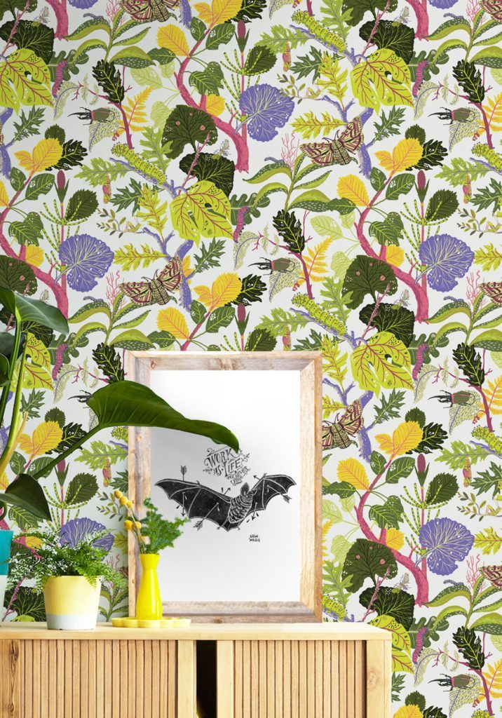 A colorful wallpaper called Caterpillar which displays a lively botanical trail of linear leaves, flowers, caterpillars and butterflies created in collaboration with Llewellyn Mejia