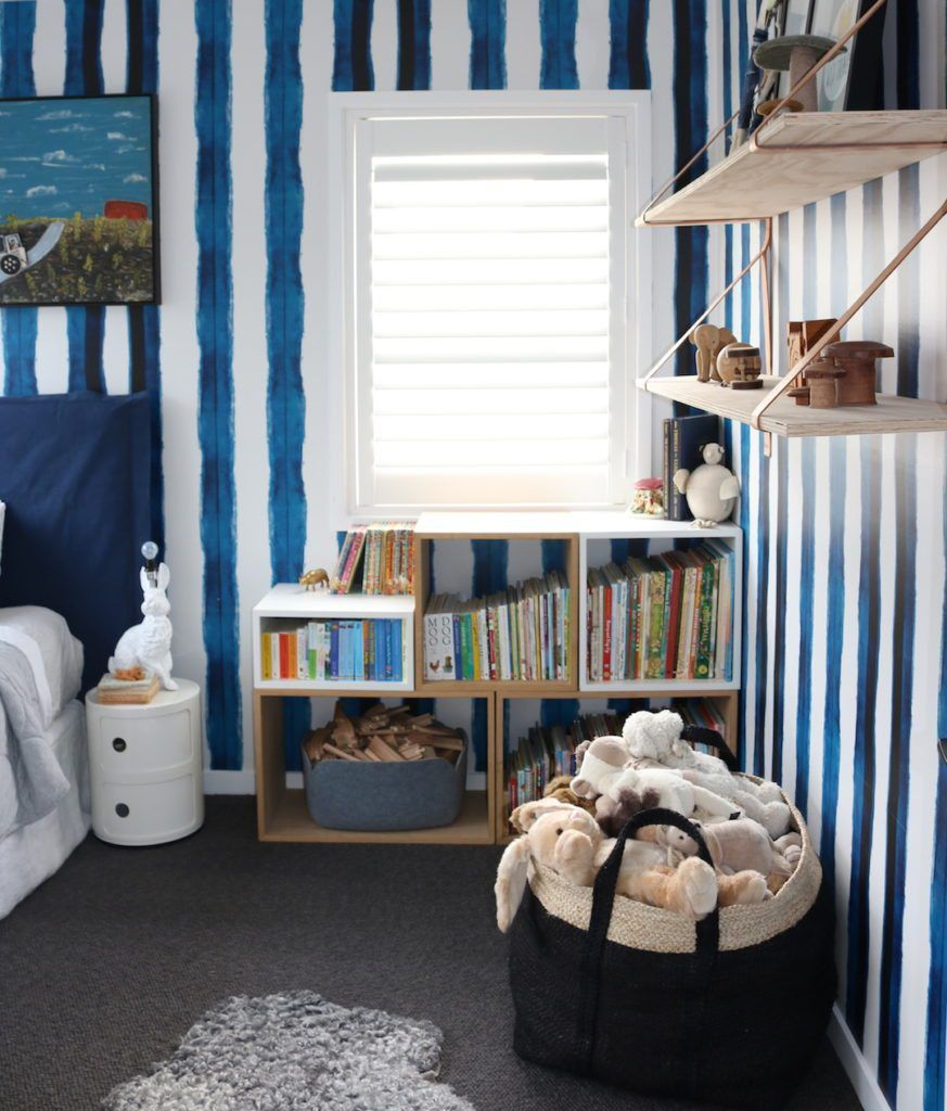 Boys bedroom with Shibori Stripe Wallpaper hung vertically with a basket of stuffed animals and a bookshelf full of childrens' books.