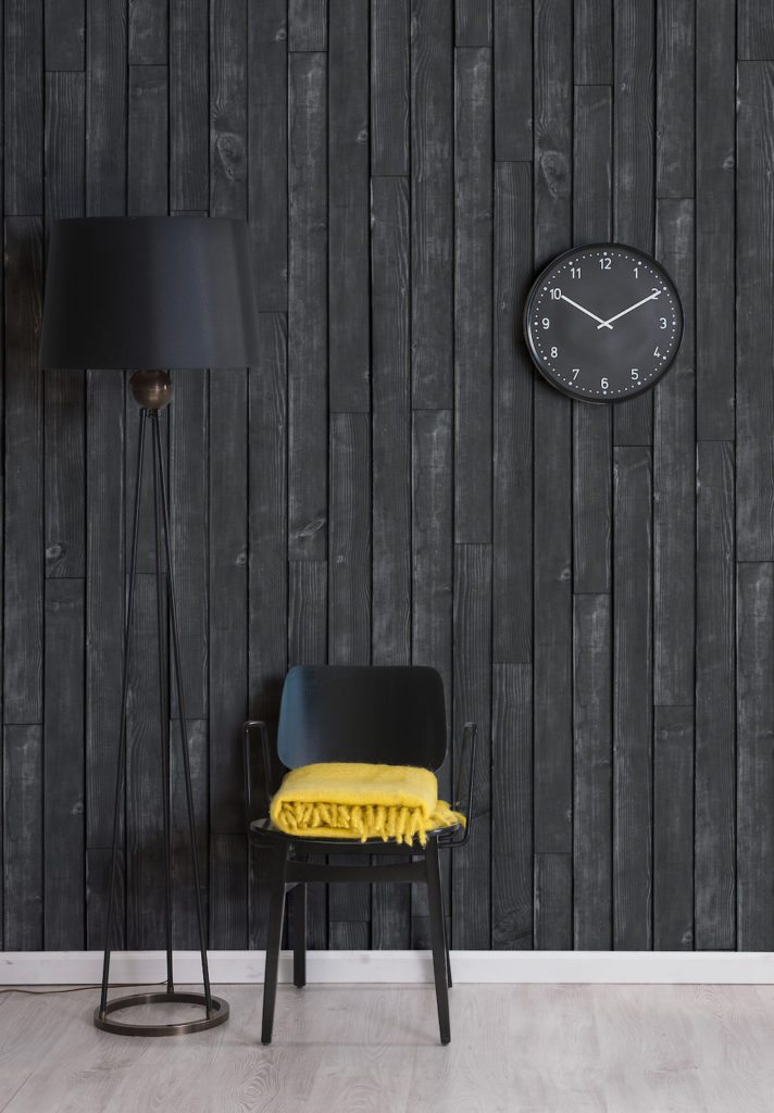 Black Wooden Boards Wallpaper.  Wallpaper with black faux timber look with black lamp shade, black lamp stand, black wall clock and black chair and yellow blanket