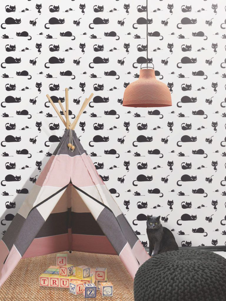 White Wallpaper with Black Cats called Meow from Milton & King.  In front of the wallpaper is a striped tent, letter blocks on the ground a black crochet stool and a black cat.