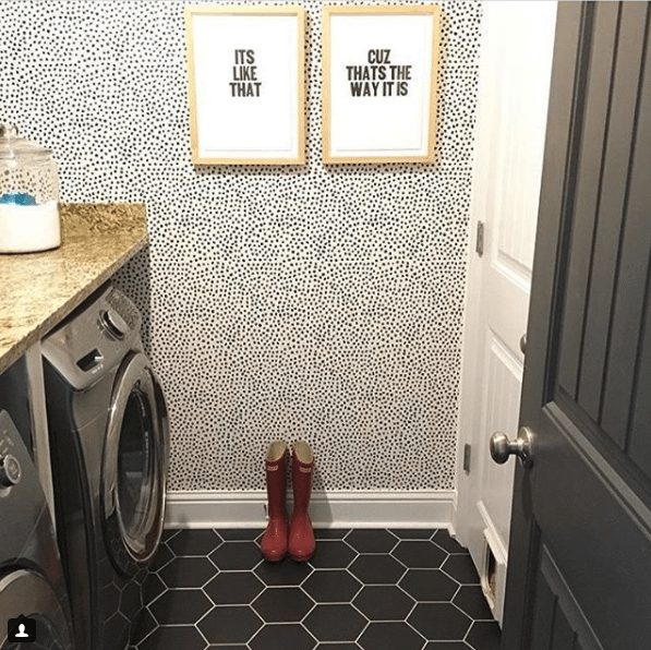 "a laundry room with a dark metallic washer and dryer on the left and a white door on the right. the floor is a black geometric tile. on the far wall is wallpaper called Leo's Spots wallpaper manufactured by Milton & King and designed by Jillian Harris. On the wallpapered wall are two pictures framed that say ""Its Like That"" and ""Cuz Thats The Way It Is"". On the floor are red gumboots."