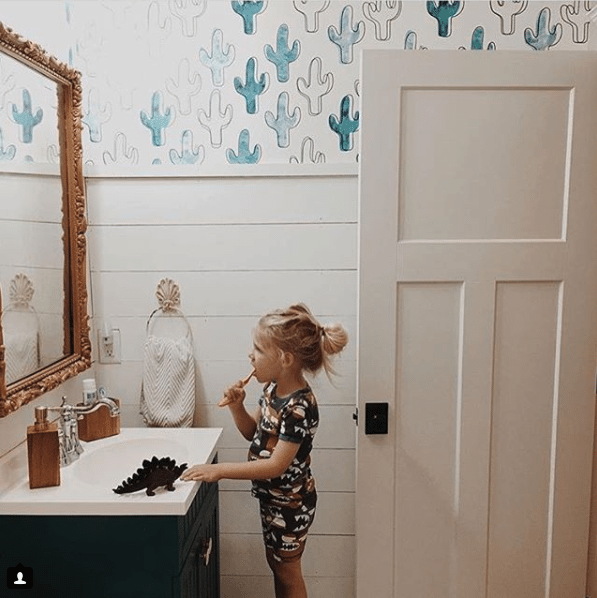 a young blonde long-haired boy brushing his teeth in front of a sink with white top on top of black cabinetry. He is looking into a mirror with a ornate gold frame. behind the boy is a wall with white horizontal timber on the bottom and on the top is blue and white Cactus Wallpaper by Milton & King.
