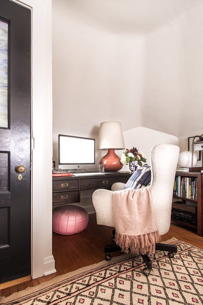 photo depicts a wide shot of an office desk with an orange lamp on the right and a computer monitor in the middle. In front of the desk is a white chair with a light colored blanker over the left arm. On the right is a small book shelf. On the floor is a tan colored carpet with small pink diamond shapes