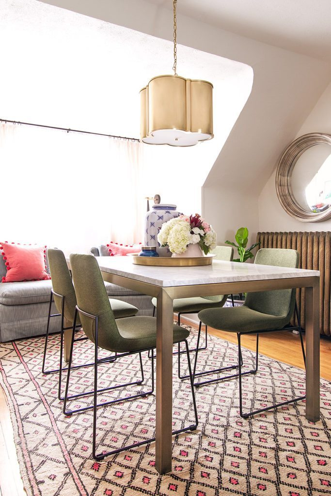 A dining table with marble top and brass frame and legs. Four olive green mid-century modern style chairs are around the table with a brass pendent lamp hanging from the ceiling. The table sits on top of Moroccan wool rug