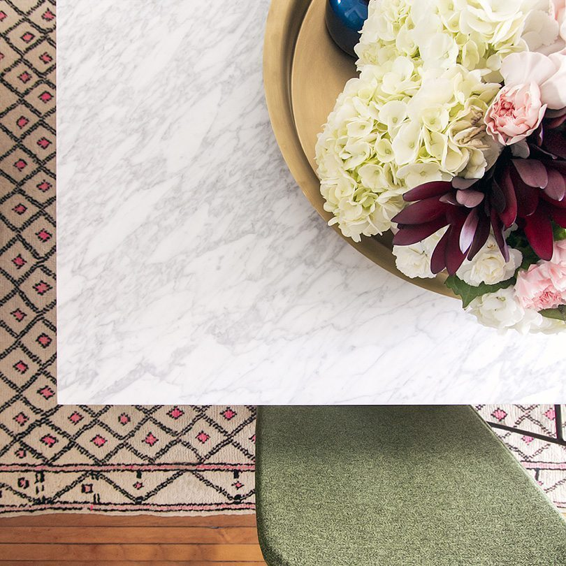 close up overhead photo of the edge of the marble topped dining table. In the center is an arrangement of florals with pink, white and red flowers.