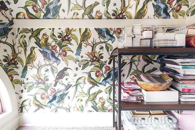 close up of Orinthology wallpaper by Milton & King with numerous colorful birds. On the right is a walnut shelf stacked with fabric samples, books and magazines