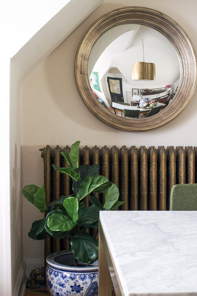 on the bottom left is a blue traditional planter with a large green leafy plant. On the wall is a circular convex mirror hanging above a brass wall heater. The marble top dining table is in the foreground