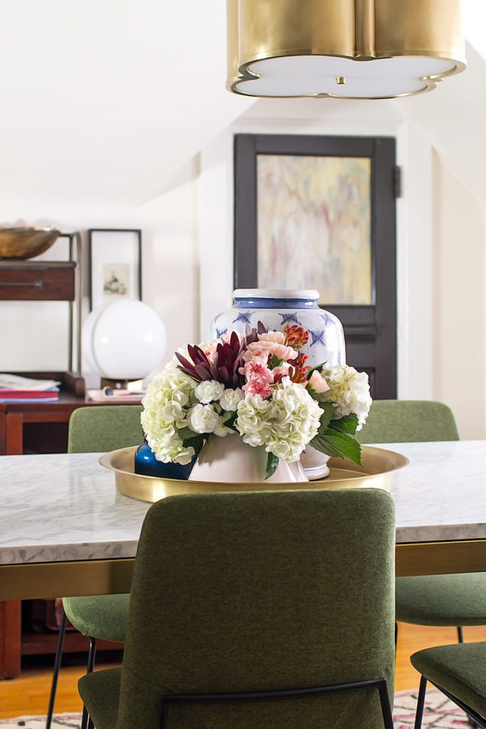 A close up shot of center piece of white, pink and red flowers on the table in the middle of the room. In the background is a blurred view of the door. In the foreground you can see the back of one of the olive green chairs