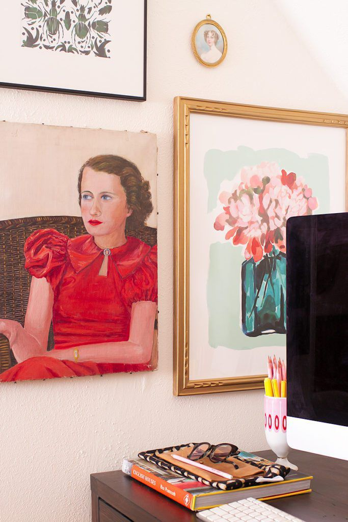 A close up shot of the art on the wall beside the desk. Show is a vintage painting of a woman from the 1930's. Above that is a print design of beetles. To the right of the beetle print is a small oval portrait of a woman. And below that is a gold framed painting of a pink floral bouquet in a blue vase.