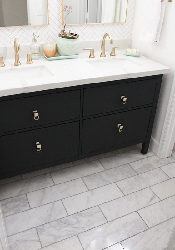 photo is focused on the dark cabinetry of the vanity which looks like it is painted black. It is on a marble tiled floor. On top is a his and hers sink with brass accents and the back wall has Tile Progress wallpaper from Milton & King