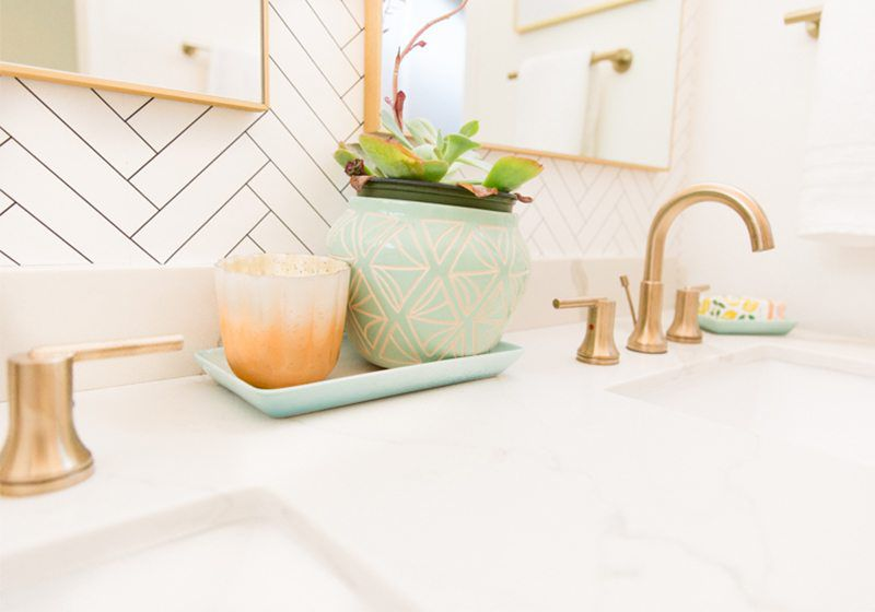 Close up shot of some plant and candle accents on the sink. On the right is brass plated faucet and handles and in the background is Tile Progress Wallpaper by Milton & King