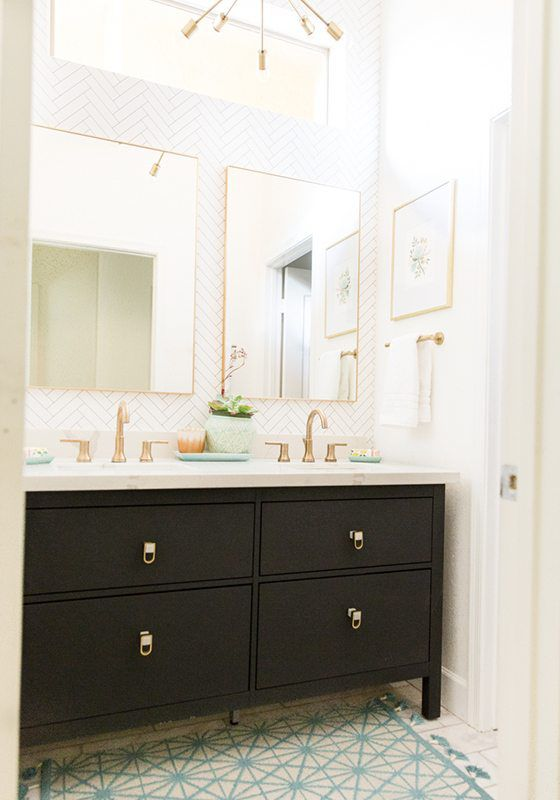 Wide shot showing the guest bathroom remodel with brass sink accents, white painted walls and dark painted vanity.