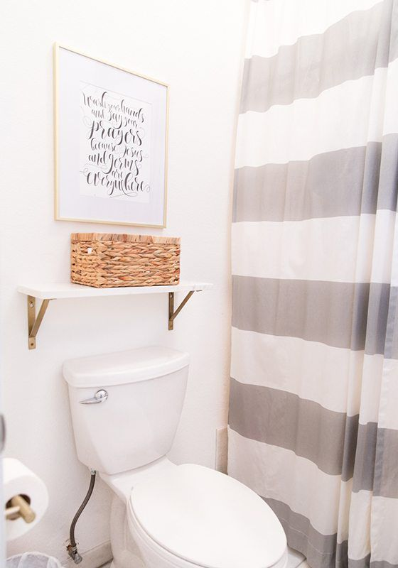 toilet with a shower on the right. The shower has a thick horizontally gray striped shower curtain. Above the toilet is a shelf with a whicker basket for storage and a picture above