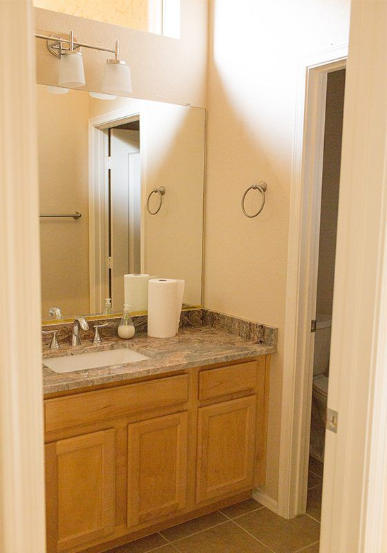 before the guest bathroom remodel photo showing light wood vanity with bare walls and beige marbled counter top