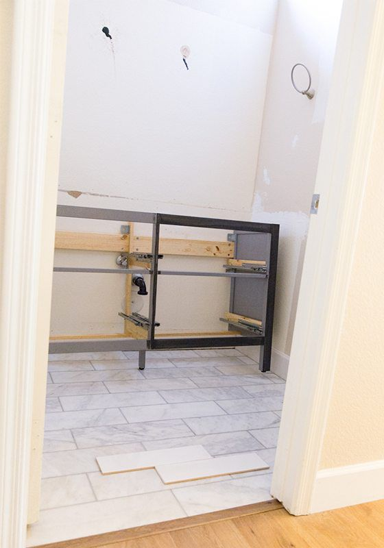 Picture of the bathroom with the remodeling in progress. A frame of the cabinet vanity