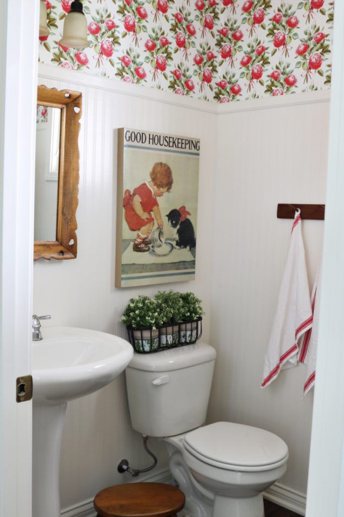 vintage bathroom with floral wallpaper around the top of the room.