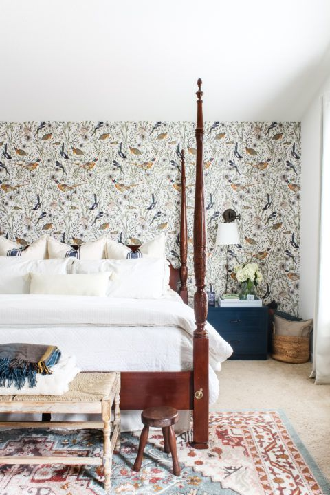 Woodland Birds wallpaper in a bedroom behind a bed with white linens. Very tall wooden bed posts at each corner of the bed.