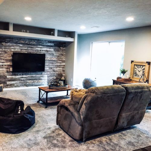 Rustic Wood Panels Wallpaper, wood wallpaper behind a tv screen in a living room with two recliner chairs and a rustic wood coffee table.