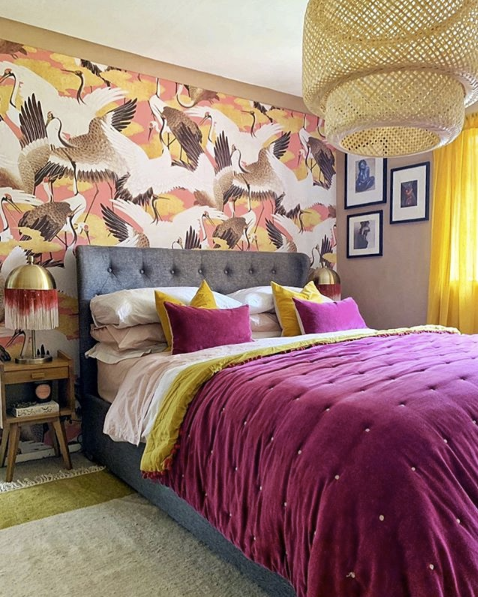 Pink Cranes Wallpaper behind a bed with a grey headboard. Gold and purple pillows are on the bed.