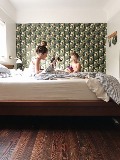 Dandelions Wallpaper on a wall beside a bed with two kids playing in the bed. Dark wood floors