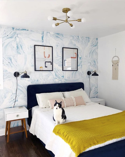 Shoreline blue wallpaper in guest bedroom behind bed with dark headboard. there is a cat on the bed looking at the camera and a golden throw blanket at the foot of the bed.