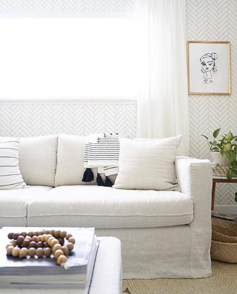 Tile Progress Wallpaper, neutral wallpaper featuring a herringbone pattern behind a white sofa. Living Room Wallpaper
