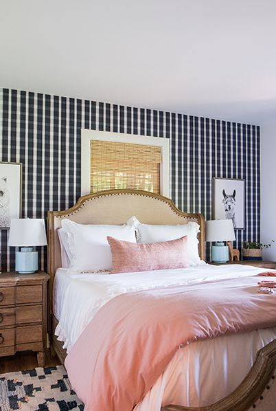 Bedroom with Bedroom wallpaper in a plaid pattern called monarch from Milton & King. A Queen sized bed with white and pink linen. Two bedside tables with pink flowers on the left and two black and white photos of llamas above each bedside table.