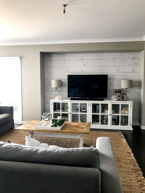 Whitewashed Timber wallpaper behind a television with a gray sofa in the foreground. there is a twill area rug on the floor