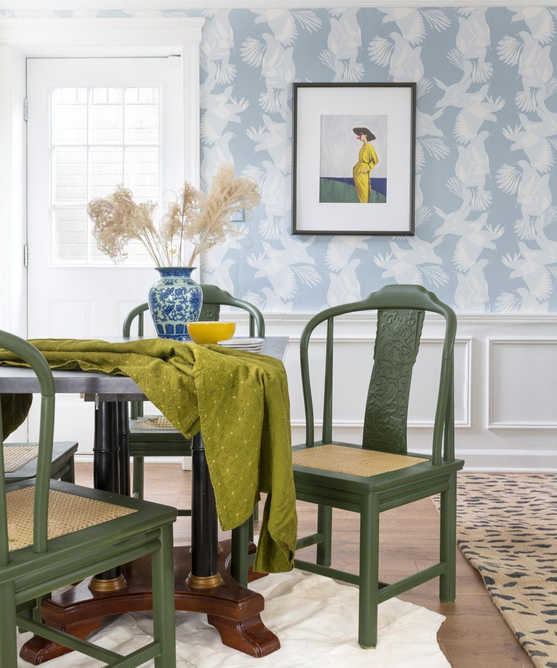 Magpie Wallpaper • Australia Collection by Kingdom Home • Blue Wallpaper • Bird Wallpaper • Photo by Jewel Marlowe • Table setting with two green chairs in front of a wall covered in wallpaper on the top with wainscoting on the bottom