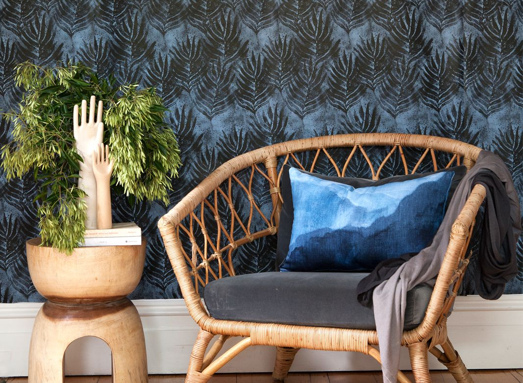 Shibori Leaf Wallpaper Design • Dark Blue Wallpaper behind a short wicker chair on the right and a green shrub on the left. In front of the green shrub are two carved wooden hands
