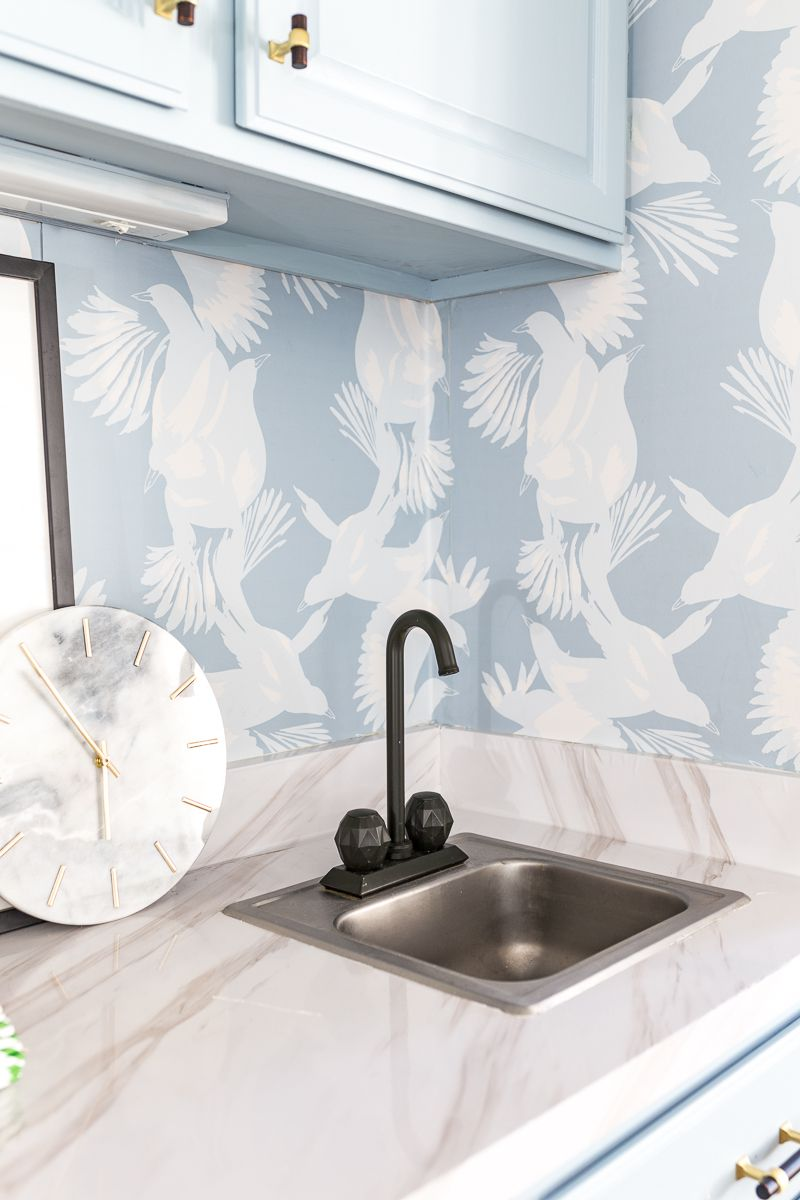Jewel Marlowe Basement Makeover • White kitchen countertop with a marble clock and blue magpie wallpaper from Milton & King