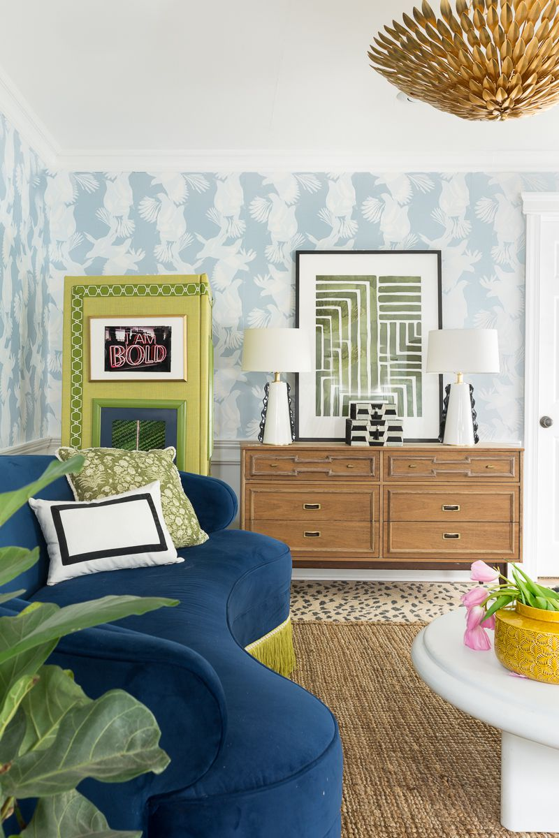 Jewel Marlow Basement Makeover • a dark blue sofa with lime green fringe sits in front of a lime green room divider. There is light blue Magpie Wallpaper from Milton & King on the back wall