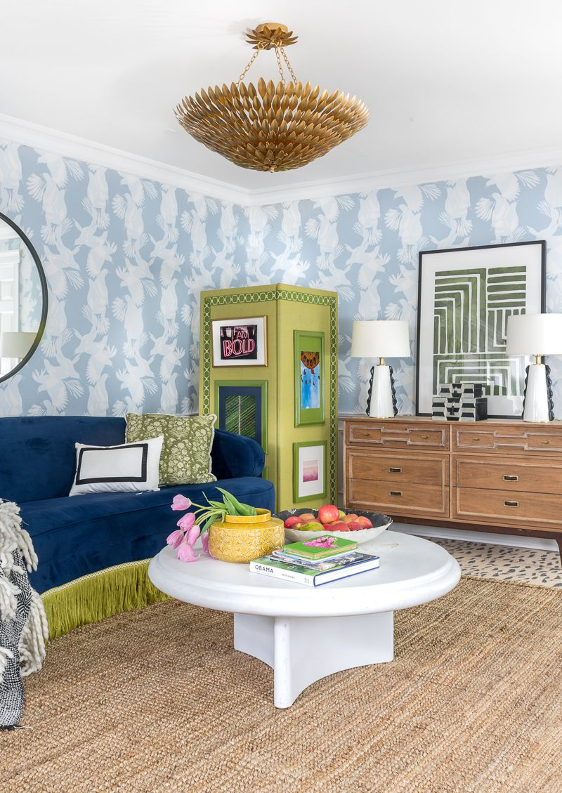 Jewel Marlowe Basement Makeover • A round white coffee table has an Obama book on it and pink tulips • Behind it is a blue sofa, a green room divider and light blue Magpie wallpaper in the background