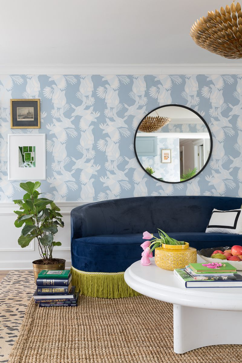 Jewel Marlow Basement Makeover •There is a leopard area rug a white round coffee table, a blue sofa and Magpie Wallaper from Mliton and King on the back wall with a big circular mirror mounted on the wall