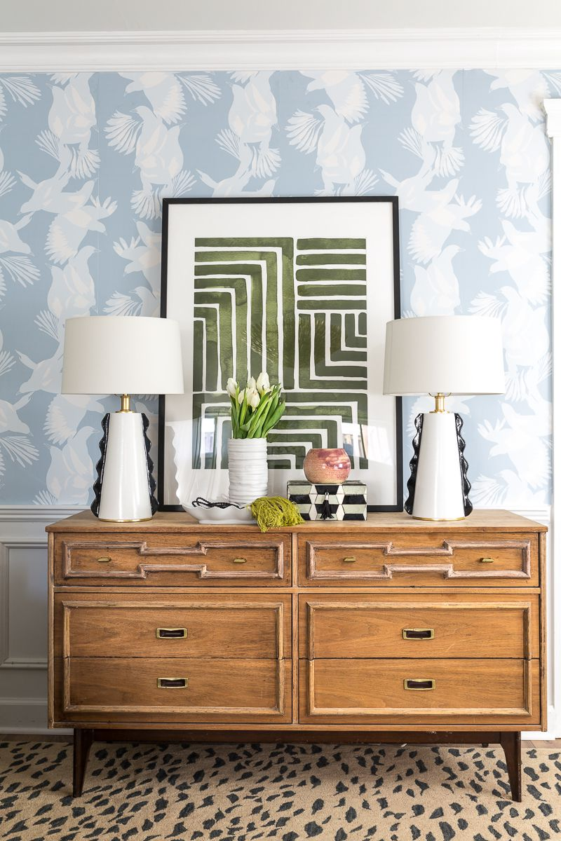 Jewel Marlowe Basement Makeover • a light brown wooden dresser has two white lamps on top and a piece of art and light blue magpie wallpaper from Milton & King