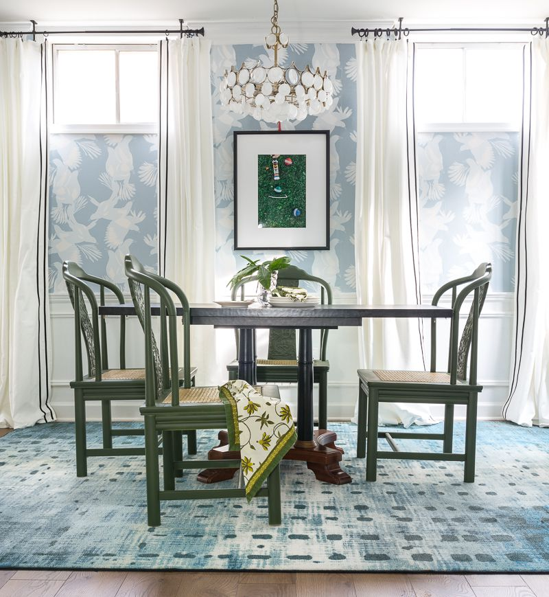 Jewel Marlowe Basement Makeover • A blue carpet with a kitchen table with green chairs and light blue magpie wallpaper from Milton & King on the wall