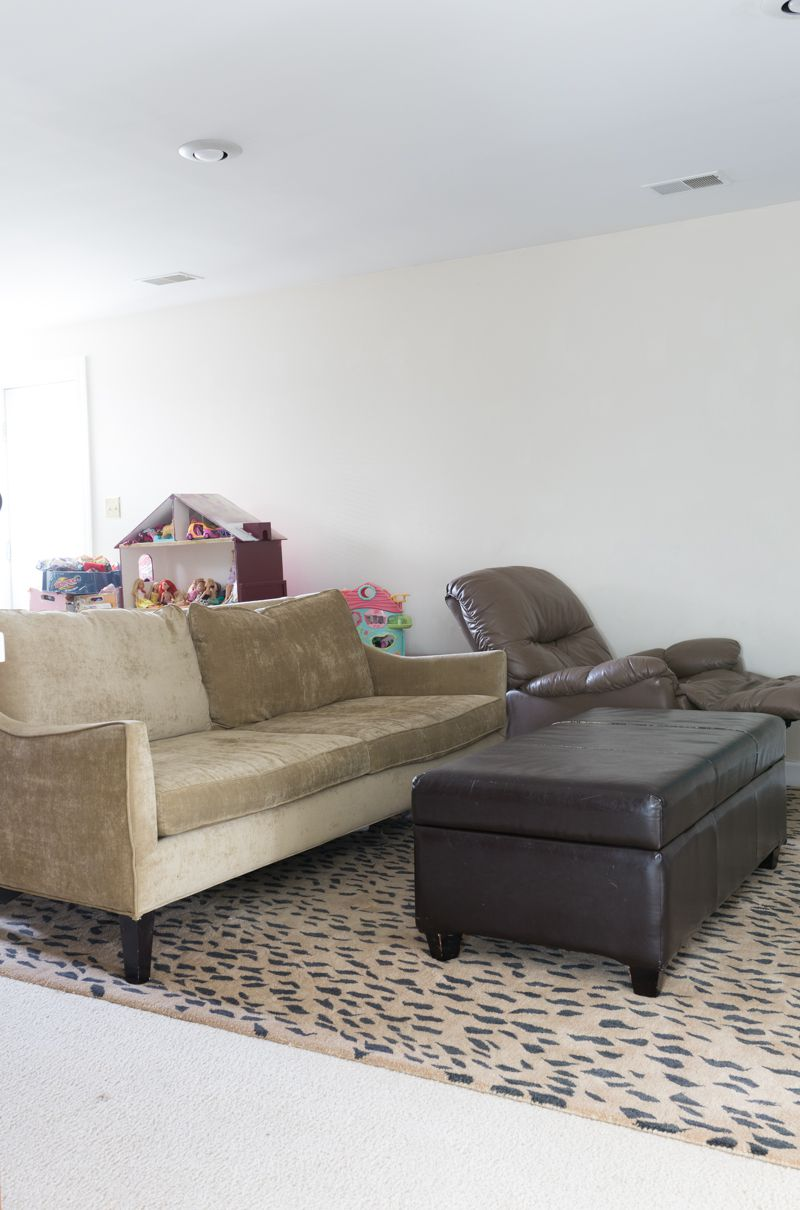 Jewel Marlow Basement Makeover • A beige couch is on a leopard rug with a dark brown leather ottoman and blank white walls in the background