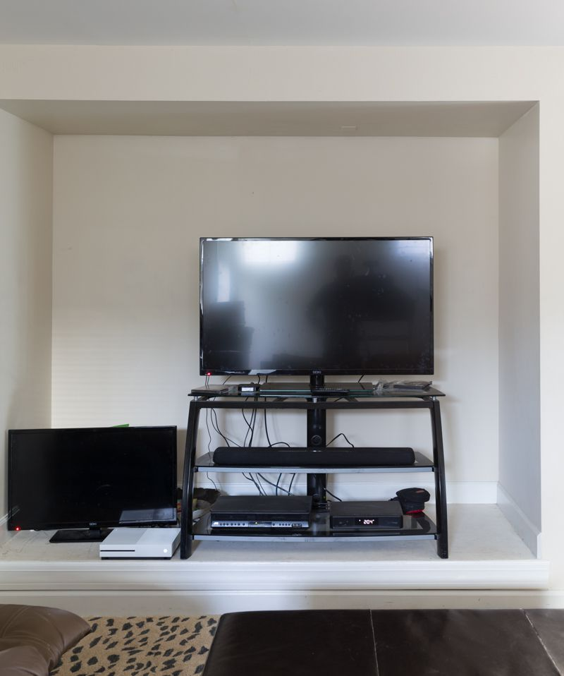 Jewel Marlow Basement Makeover • A TV sits on a black minimal stand against a white wall