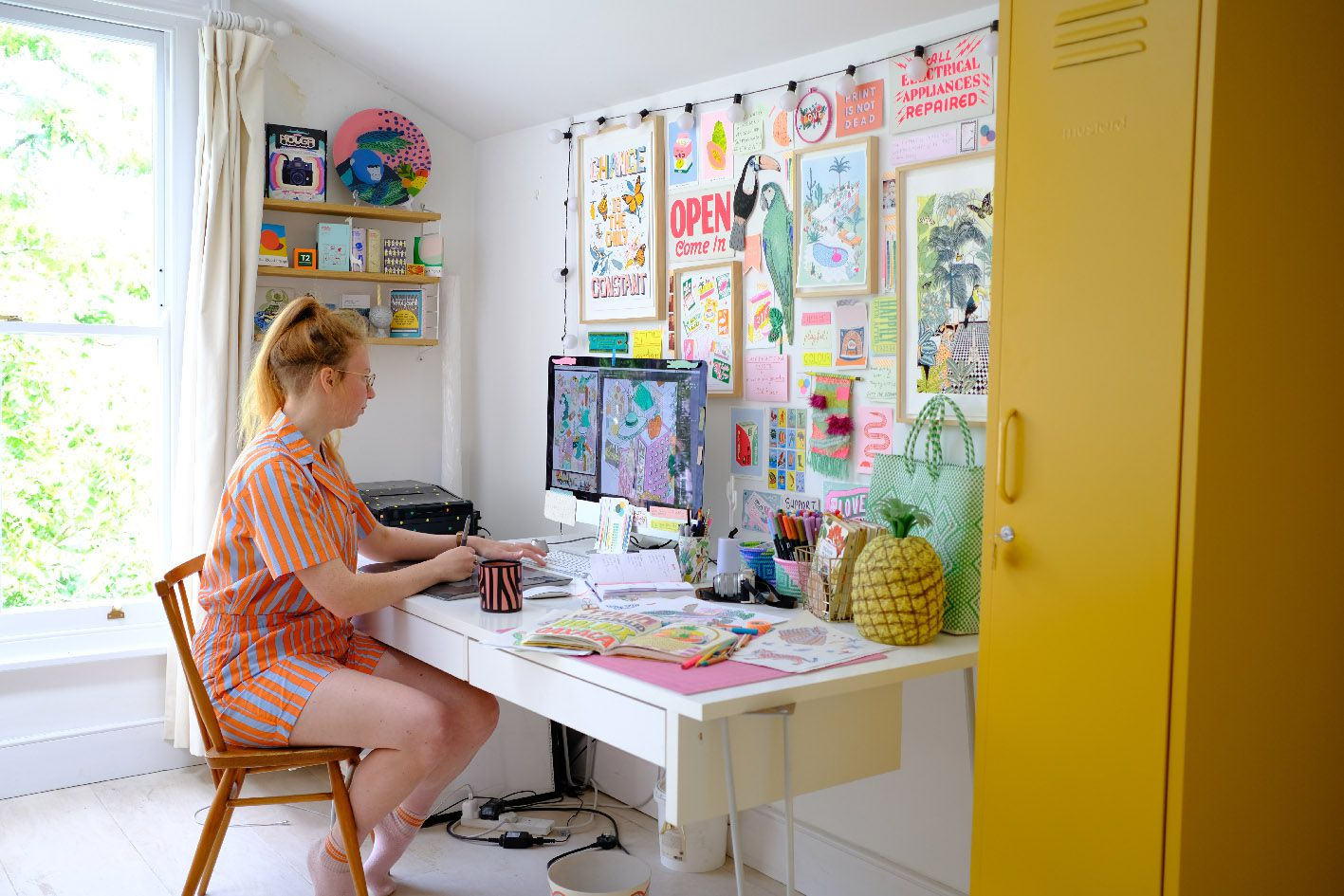Jacqueline Colley illustrating colorful wallpaper designs in her home studio