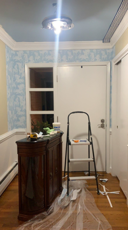 installing light blue wallpaper. there is plastic on the floor to protect it from any glue that might drip
