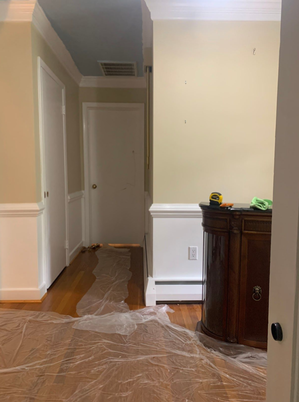 Picture of an entry way and a hallway with bare beige walls and white paint just below the chair rail. There is plastic on the floor in preparation for painting.