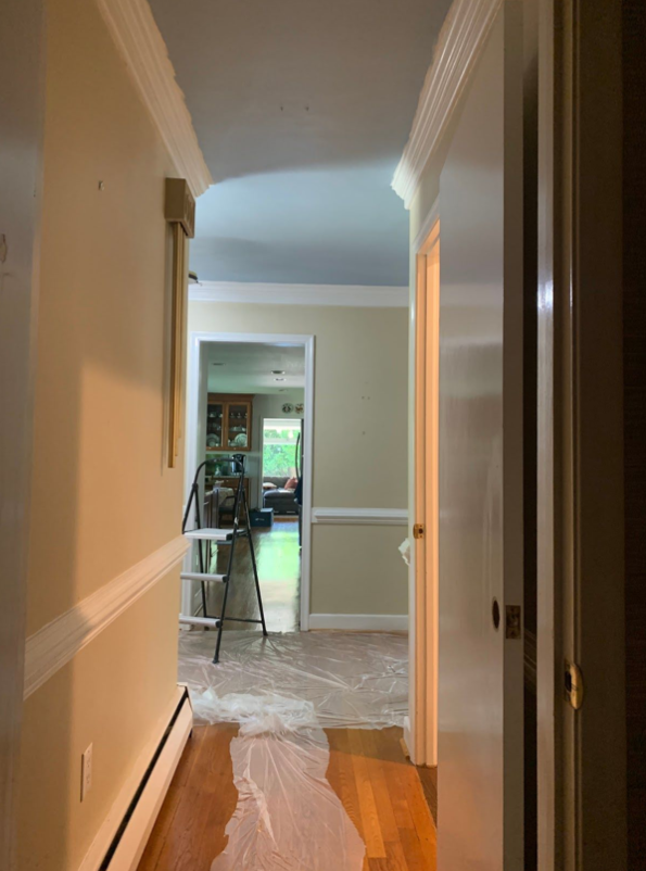 This picture is of a narrow hallway with the walls painted beige and the chair rail painted white