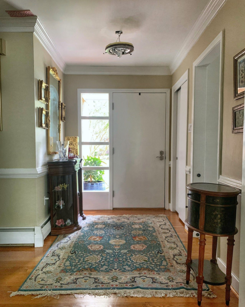picture of entry way. there is a white front door. there is a turquoise area rug on the floor. There are golden framed pictures on the left wall.