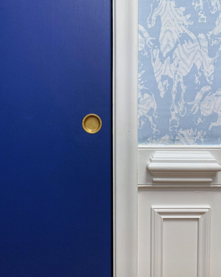 Close up image of newly painted blue door and the Stampede wallpaper from Milton & king above the wainscoting