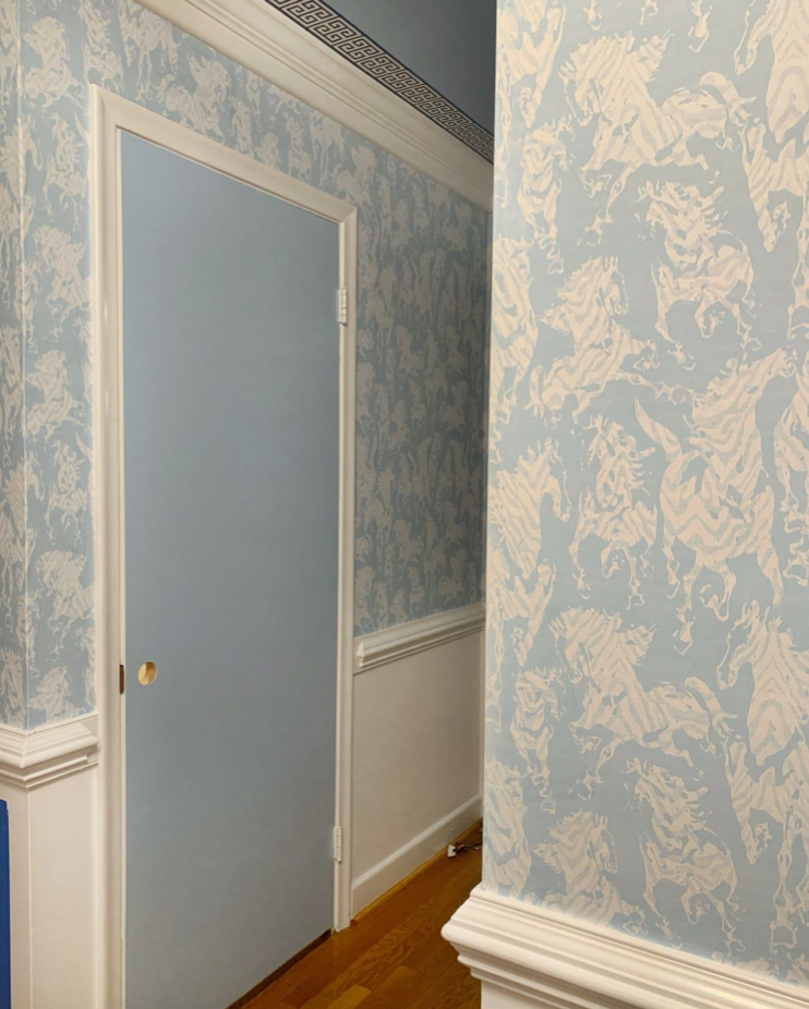 Hallway with Stampede Wallpaper by Milton & King. The wallpaper is light blue with horses. The doors are also painted light blue to match the wallpaper.