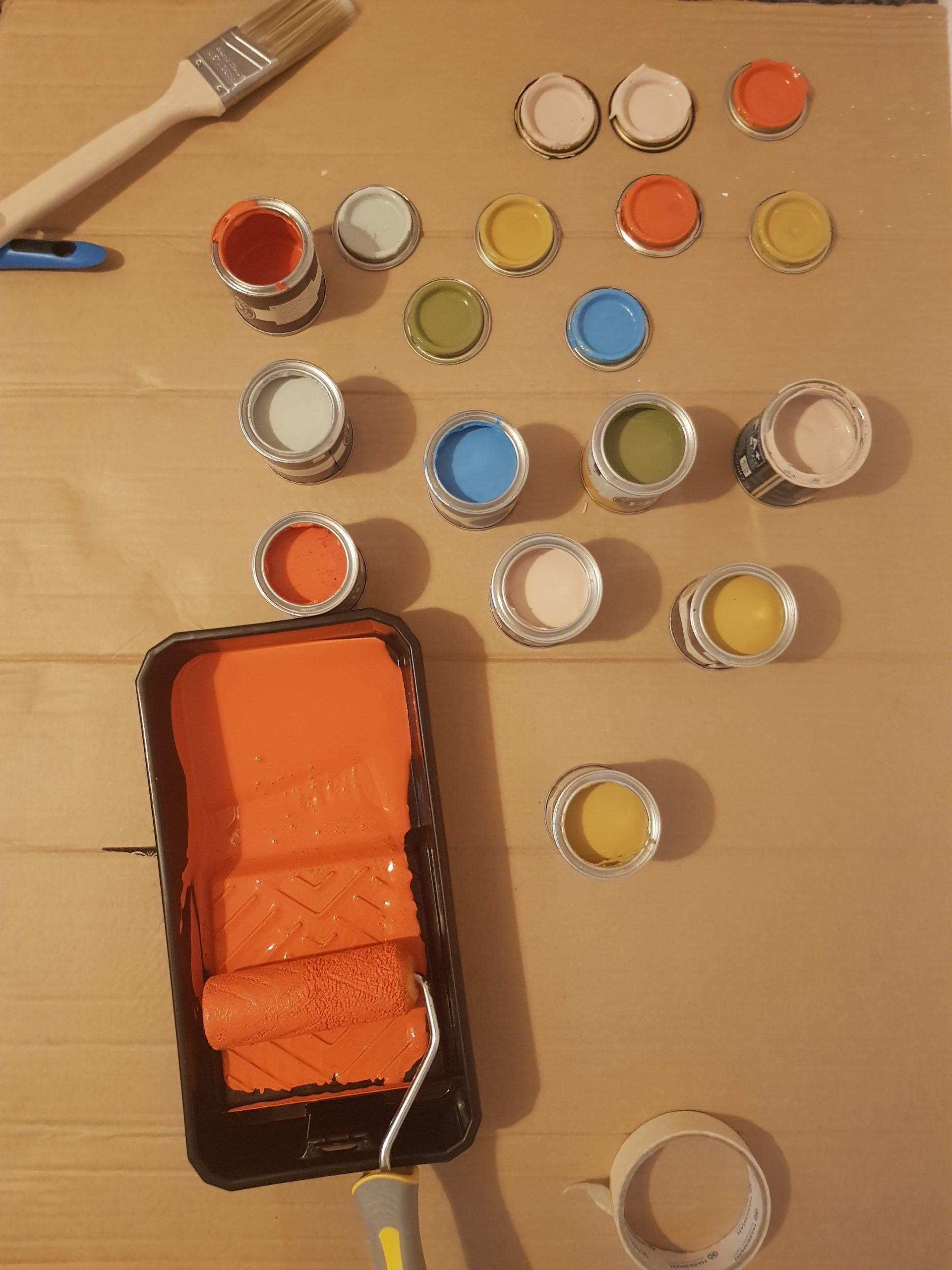 A paint tray with orange paint and several other cans of paint with various colors